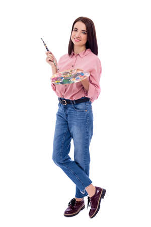 full length portrait of beautiful woman with palette and paint brush isolated on white background Фото со стока