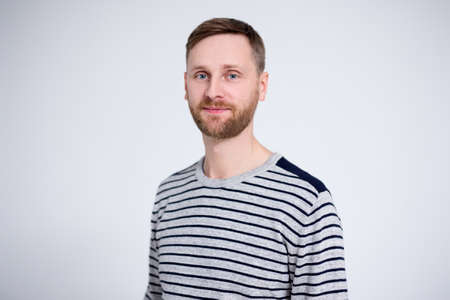 portrait of handsome bearded man posing over white background