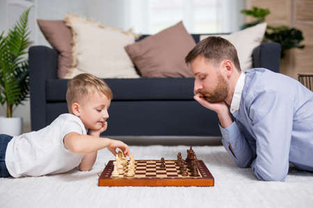 portrait of young father playing chess with his little cute son at home Фото со стока