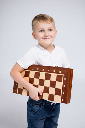 portrait of cute little boy holding chess board over white background Фото со стока