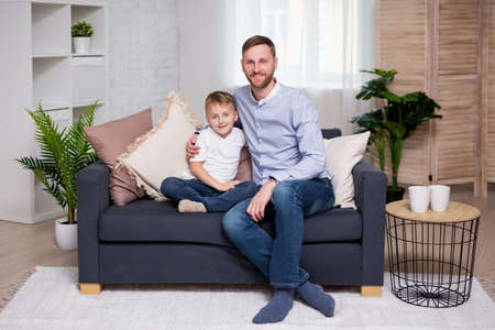 portrait of happy father with little son sitting on sofa at home