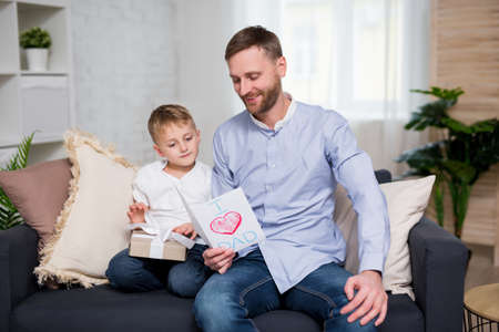 Fathers day concept -  little boy giving handmade greeting card and gift box to his father at home