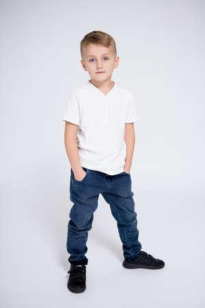 full length portrait of cute little boy posing over white background Фото со стока