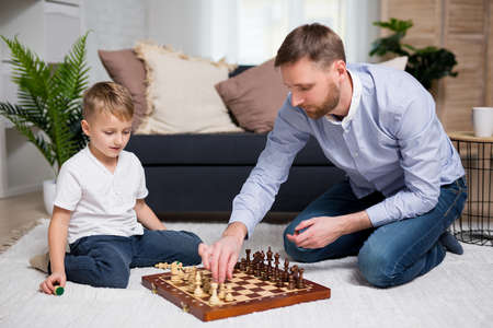 young father playing chess with his little cute son at home Фото со стока