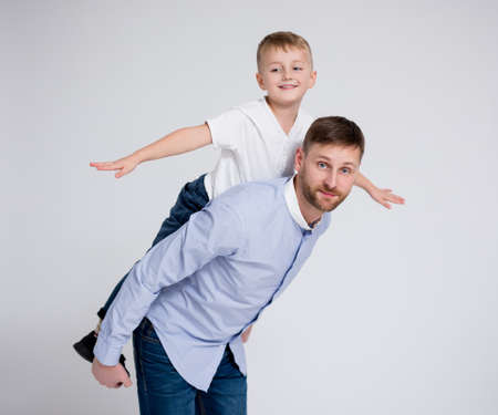 happy family portrait - father with cute little son posing over white background