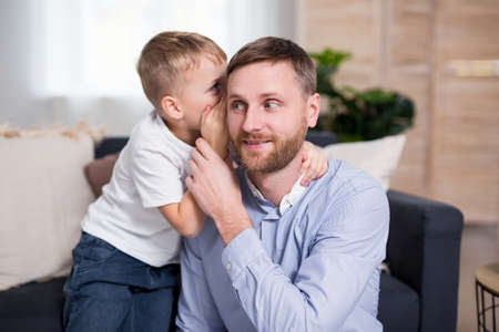cute little son whispering a secret at ear to his daddy Фото со стока