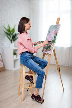 art, creativity and inspiration concept - full length portrait of young beautiful woman artist painting at home or studio