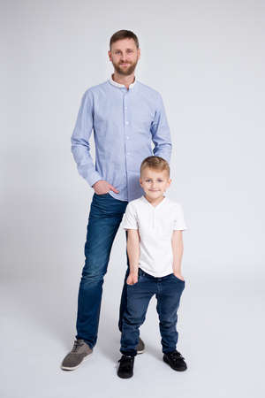 full length portrait of young father and son posing over white background Фото со стока