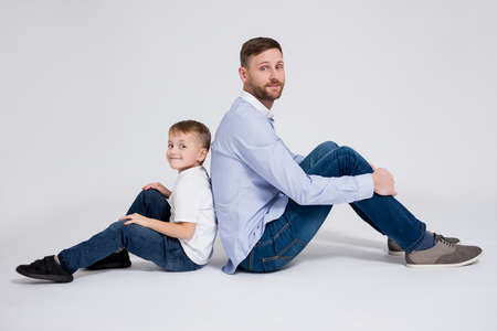happy family portrait - father with cute little son sitting over white background