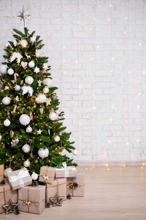decorated christmas tree, heap of gift boxes and copy space over white brick wall background with lights