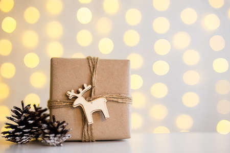 close up of gift box and fir cones over white background with copy space and garland lights