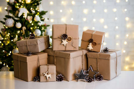 christmas background - heap of beige gift boxes near decorated christmas tree