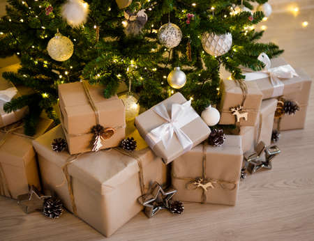 close up of beige gift boxes under decorated christmas tree with lights Фото со стока