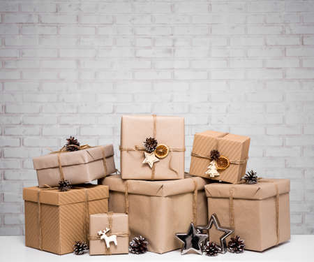 close up of beige gift boxes and copy space over white brick wall background Фото со стока