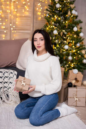 christmas and new year concept - portrait of young beautiful woman sitting with gift box near decorated Christmas tree