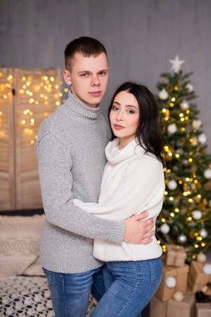 christmas, new year and love concept - young cute couple in love posing near Christmas tree Фото со стока