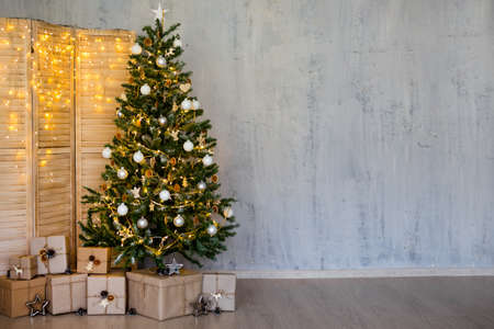 Christmas and new year background - christmas tree, heap of gifts, folding screen with lights and copy space over grey wall