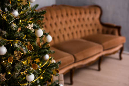 decorated christmas tree and vintage sofa in living room