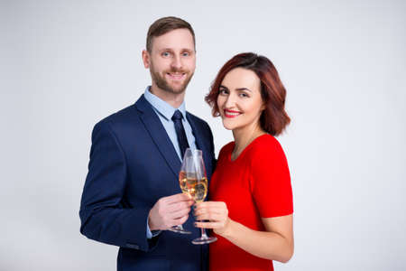 valentines day, christmas and new year concept - portrait of beautiful couple posing with glasses of champagne over white background