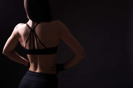 back view of sexy woman with muscular body posing over black background with copy space