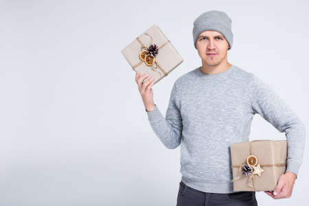 winter and holidays concept - portrait of cheerful young man in warm winter clothes posing with gift box over gray background with copy space Фото со стока