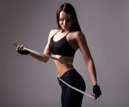 beautiful sporty woman with muscular body measuring her waistline with measure tape over gray background