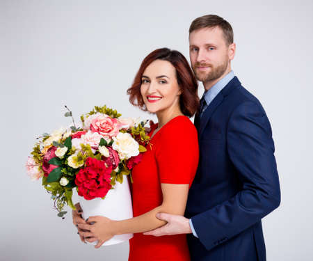 Valentines day or birthday concept - handsome man surprising his girlfriend with beautiful flowers over white background Фото со стока