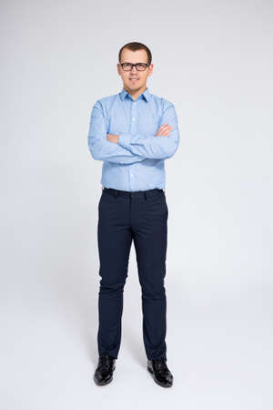 full length portrait of young businessman over gray background