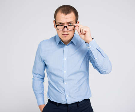 portrait of young serious businessman in eyeglasses posing over gray background