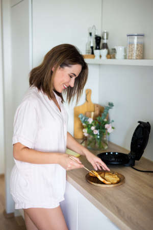 morning and breakfast concept - young attractive woman in pajamas making belgian waffles in modern kitchen