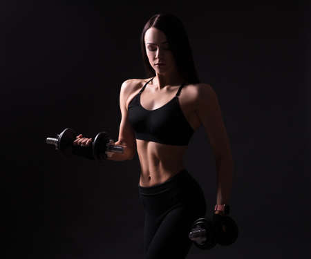 beautiful sporty woman with muscular body exercising with dumbbells over black background Фото со стока