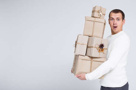 Christmas or Valentines day background - young handsome man in white warm sweater holding heap of gift boxes over gray background with copy space