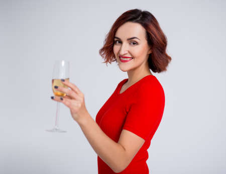 new year concept - portrait of young woman posing with glass of champagne over white background