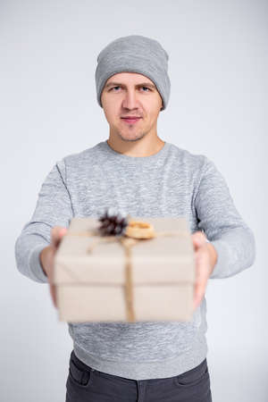 portrait of young man in warm winter clothes posing with gift box over gray background Фото со стока