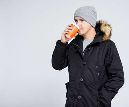 young handsome man in warm winter jacket drinking coffee or tea over gray background with copy space Фото со стока