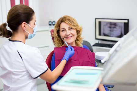 portrait of cheerful mature woman in dentist office with doctor in mask Фото со стока