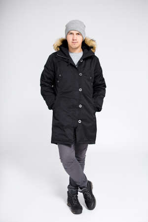 fell length portrait of young handsome man posing in warm winter clothes over gray background Фото со стока