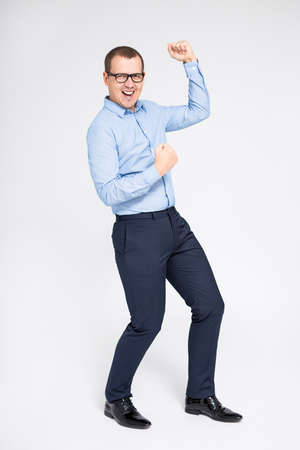 portrait of young cheerful businessman celebrating something and dancing over gray background