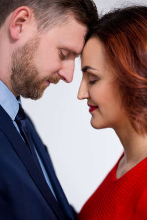 Valentine's day and love concept - close up portrait of cute elegant couple hugging over white background Stock Photo - 136523570