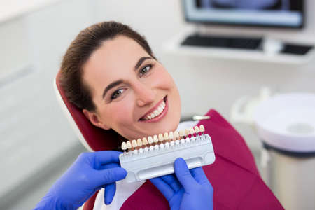 teeth whitening - young smiling woman in the selection of tooth color at dental clinic