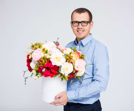 valentines day or mothers day concept - portrait of young handsome man with flowers box Фото со стока