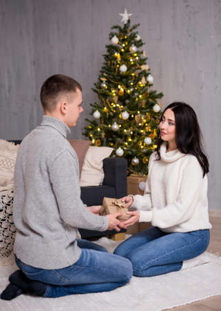 christmas, new year and love concept - beautiful woman giving Christmas present to her boyfriend in decorated living room with Christmas tree and gift boxes
