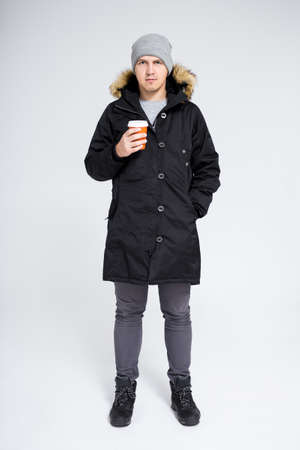 fell length portrait of young handsome man in warm winter jacket drinking coffee or tea over gray background