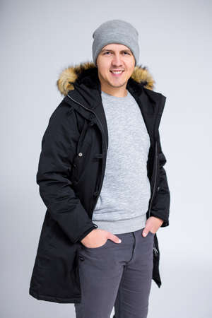 portrait of young smiling man posing in warm winter clothes over gray background