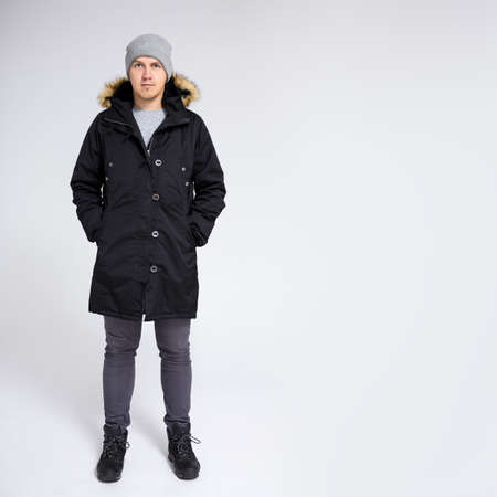 full length portrait of young handsome man in warm winter jacket over gray background with copy space Фото со стока