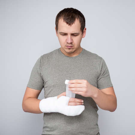 fracture and first aid concept - young man bandaging his hand after accident over gray