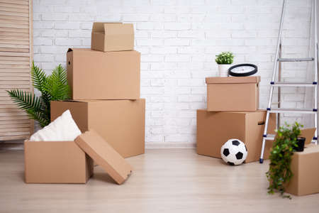 moving day concept - stack of moving boxes in new house or flat over white brick wall background