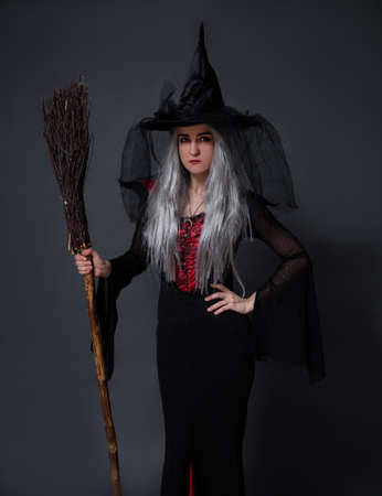 portrait of mysterious woman in witch halloween costume posing with broom over black background