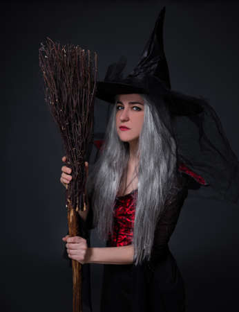 mysterious woman in black witch halloween costume and hat posing with broom over black background