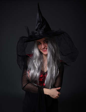 smiling woman in black witch halloween costume and hat posing over black background